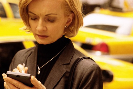 Stock Photo: 1566-033439 Woman using electronic organizer