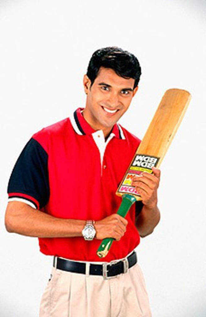 Smiling athlete holding cricket bat : Stock Photo