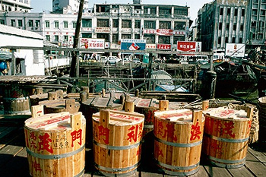 Stock Photo: 1566-054728 Wooden barrels of salted fish with ideograms at pier. Macau, China