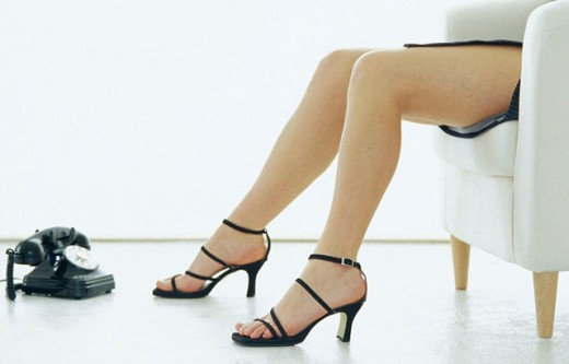 Woman´s legs, old telephone : Stock Photo