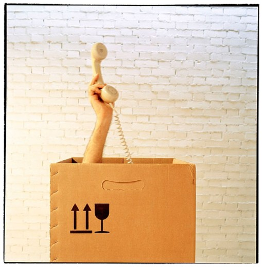 Hand with telephone from inside a cardboard box : Stock Photo