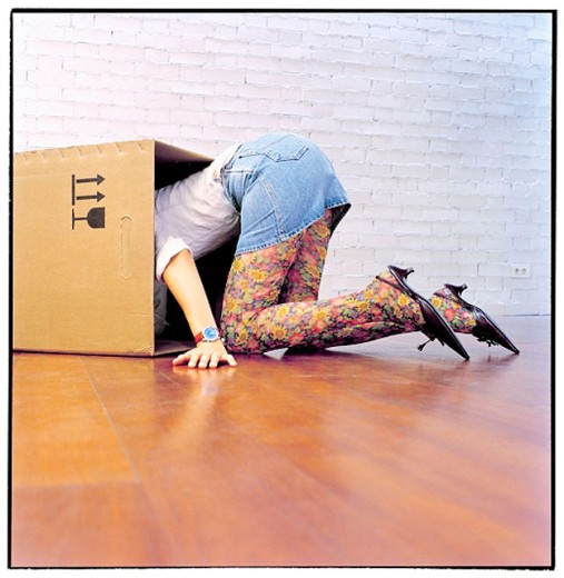 Woman looking for something in a cardboard box : Stock Photo