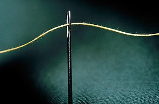 Golden thread through eye of needle. : Stock Photo