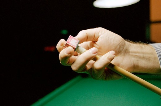 Billiards game, applying chalk to the cue tip : Stock Photo