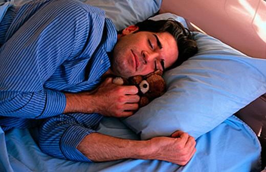 Stock Photo: 1566-0894 Man sleeping with a teddy bear