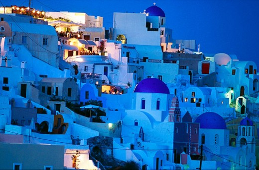 Greece, Cyclades, Santorini , White houses and blue dome church on sunset over caldeira at Oia. : Stock Photo