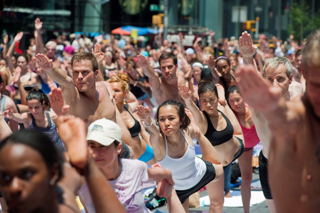 Thousands of yoga practitioners in Times Square in New York participate in a mid-day Bikram Yoga class on the first day of summer Temperatures are expected to rise into the upper 90´s today as most New Yorkers seek relief from the heat : Stock Photo