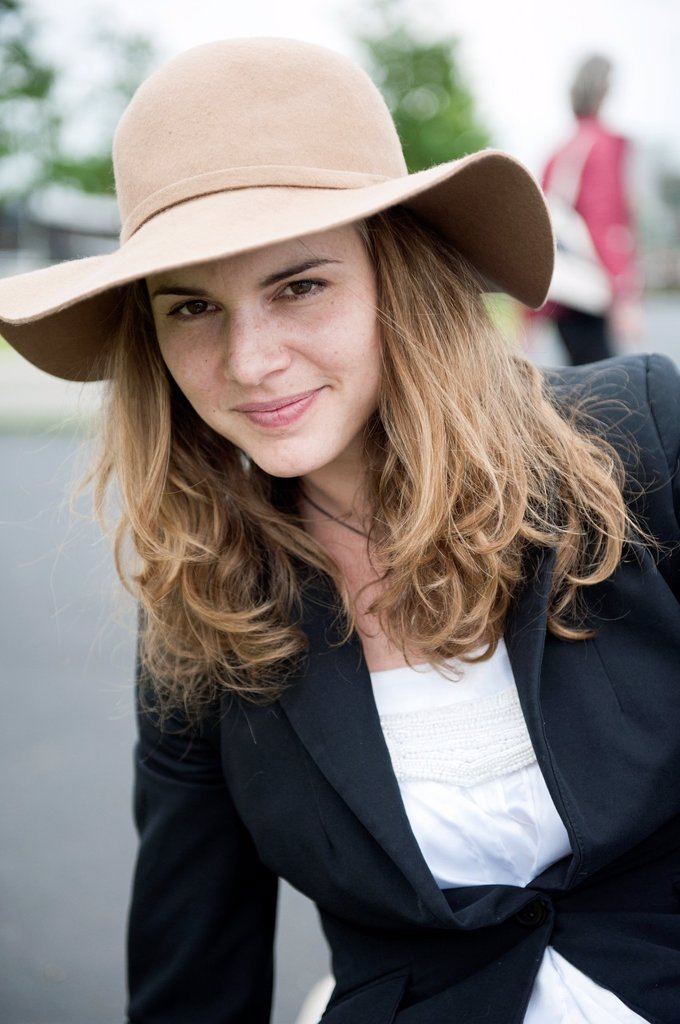 Stock Photo: 1566-1002174 Portrait of a young, attractive brunette with hat and long, strait hair.