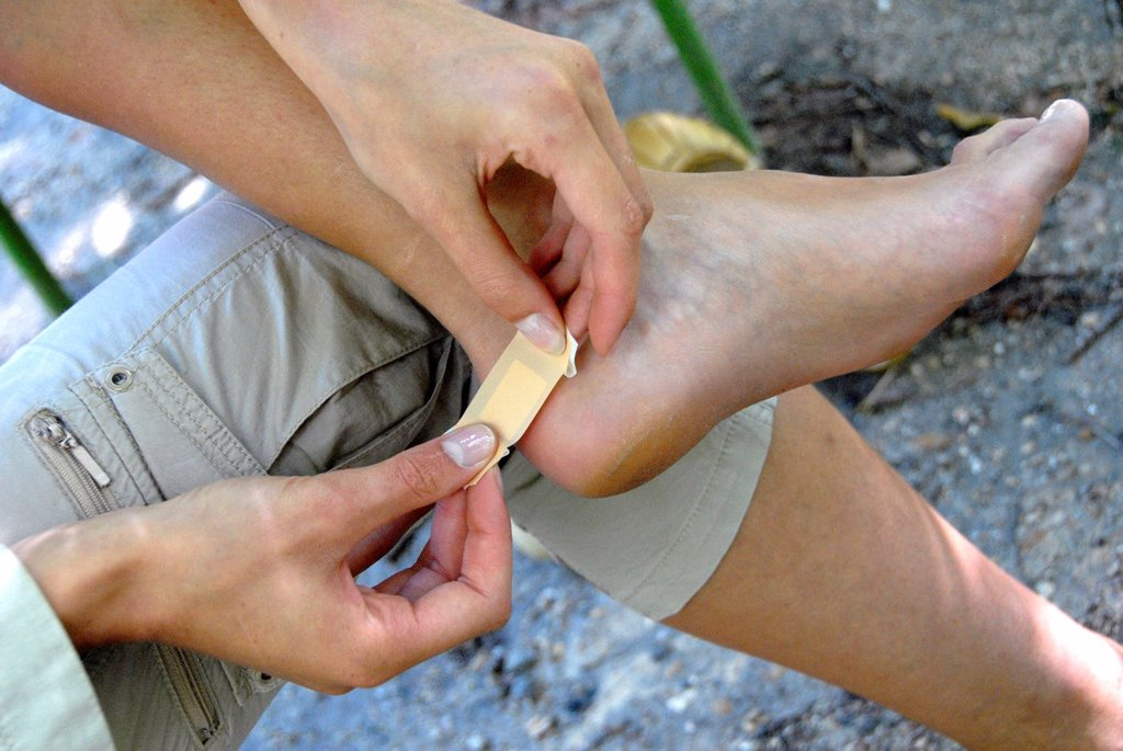 Stock Photo: 1566-1002256 Putting a bandage on foot blister