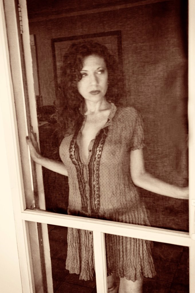 Stock Photo: 1566-1002342 Portrait of a 42 year old woman with long curly black hair in a provocative pose standing a screen door