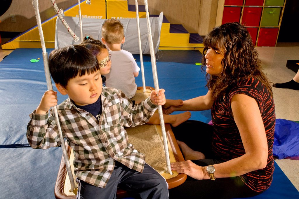 Blind and vision-impaired children ride a swing to improve their balance and body awareness in a sensory motor group at the Blind Children´s Learning Center in Santa Ana, CA : Stock Photo