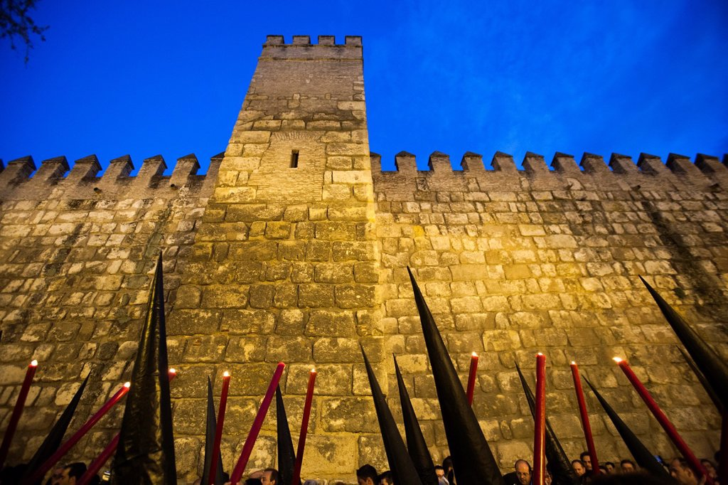 Stock Photo: 1566-1007479 the cones of hooded penitents bearing candles against the Alcazar ramparts, Holy Week, Seville, Spain
