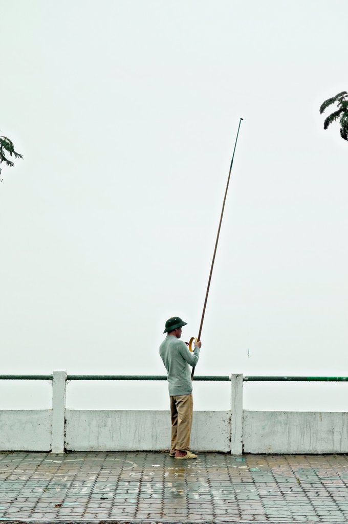 Stock Photo: 1566-1008624 A lone fisherman at at West Lake in Hanoi, Vietnam