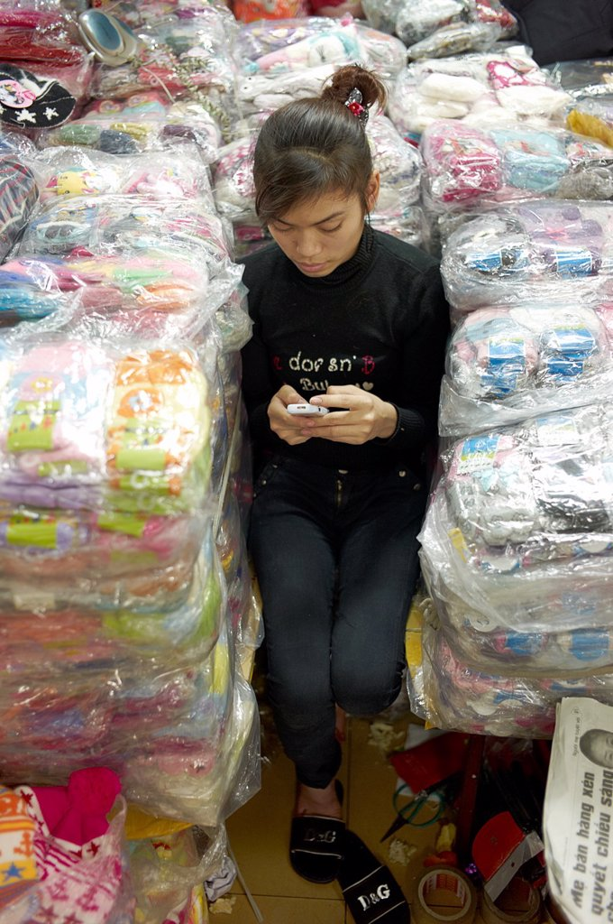 Stock Photo: 1566-1008630 A young woman playing on her cell phone while sitting in between piles of shrink wrapped clothes