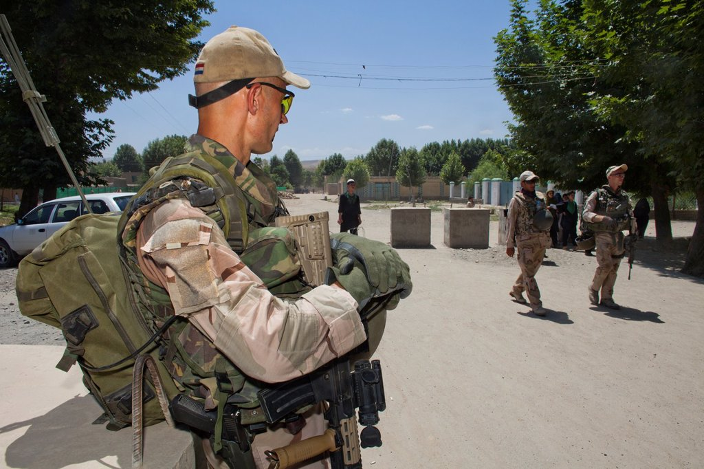 Dutch police mentors walking patrol with Afghan police officers in Kunduz : Stock Photo