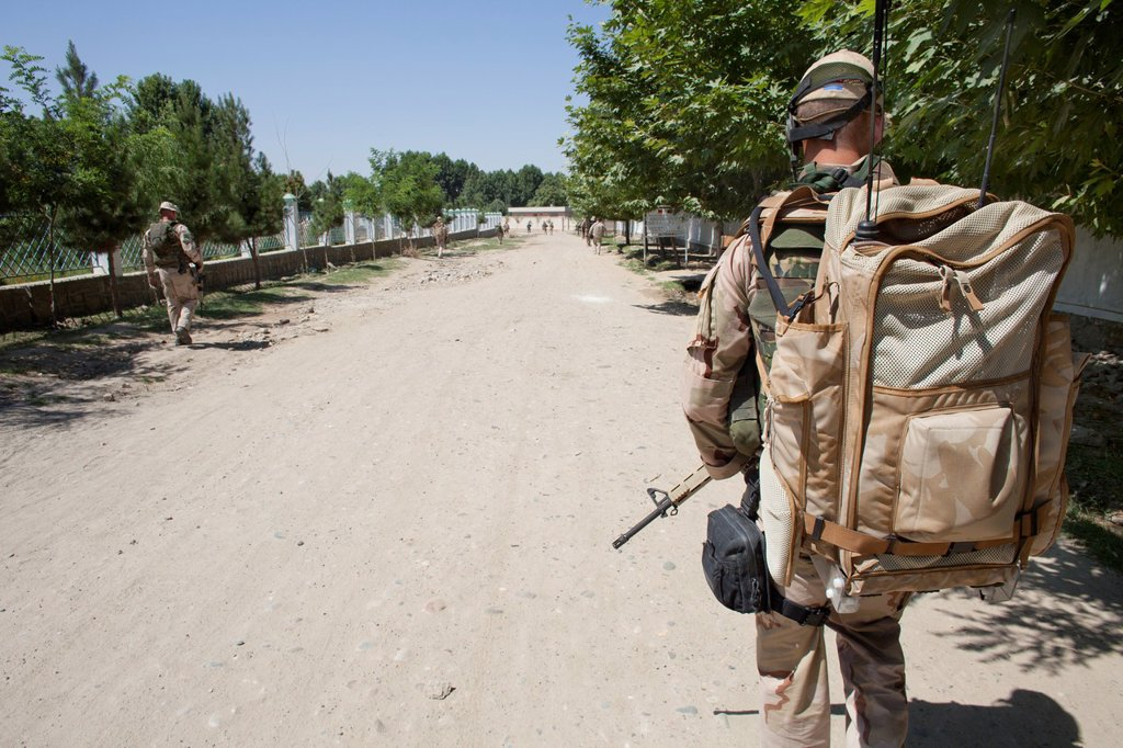 Dutch police mentors walking patrol with Afghan police officers in Kunduz : Stock Photo