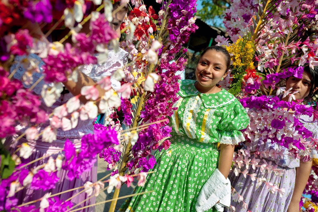Stock Photo: 1566-1012088 Salvadoran girls carry palm branches with colorful flower blooms during the procession of the Flower & Palm Festival in Panchimalco, El Salvador, 8 May 2011  On the first Sunday of May, the small town of Panchimalco, lying close to San Salvador, celebrate. Salvadoran girls carry palm branches with colorful flower blooms during the procession of the Flower & Palm Festival in Panchimalco, El Salvador, 8 May 2011  On the first Sunday of May, the small town of Panchimalco, lying close to San Salvado