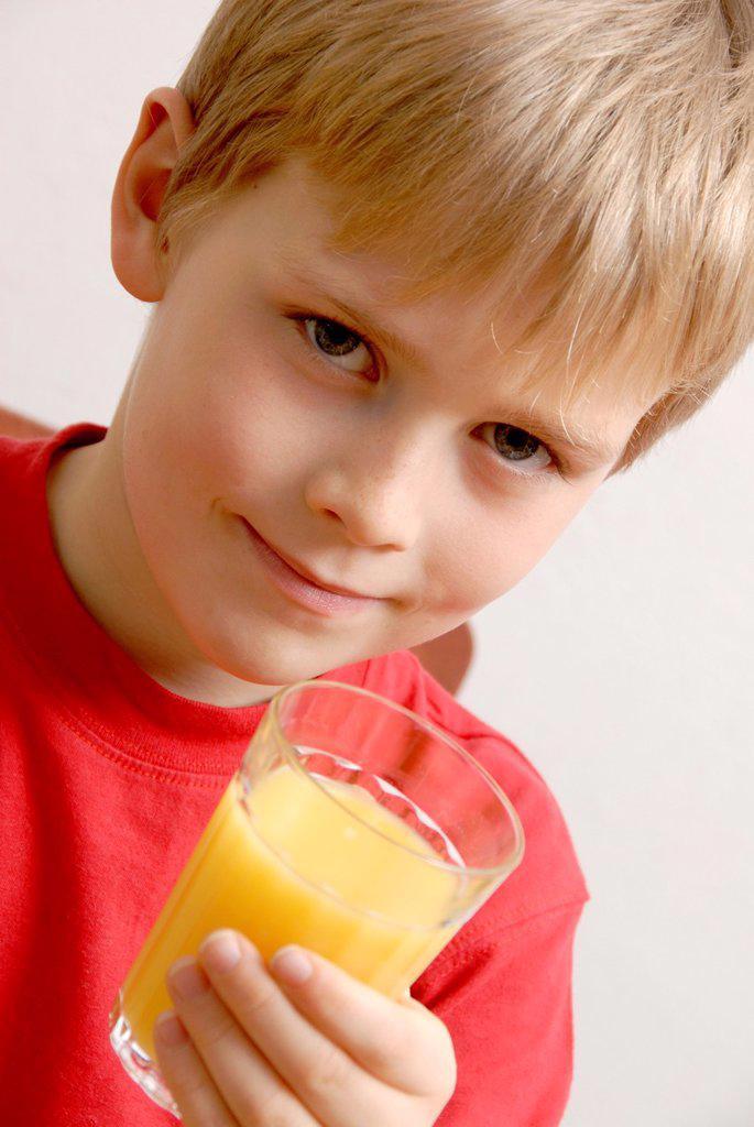 Stock Photo: 1566-1013510 Young boy drinking orange juice