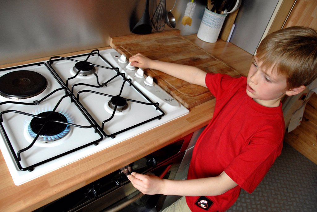 Stock Photo: 1566-1013524 Child danger  Boy turning on a hob gas ring