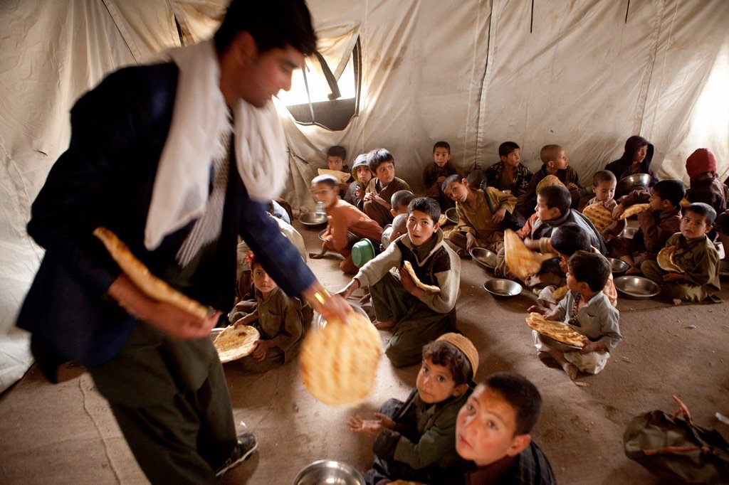 Afghan student gets food at school : Stock Photo