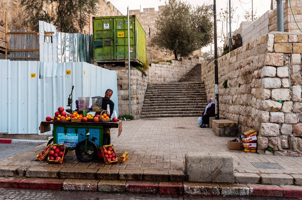 Stock Photo: 1566-1016997 Man squeezing fresh pomegranate and orange juice at a sidewalk stall, Old City, Jerusalem, Israel