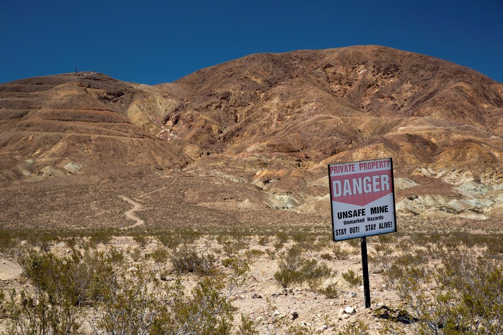 Stock Photo: 1566-1017052 Barstow, California - A sign warns visitors to stay away from unsafe mines in the Mojave Desert