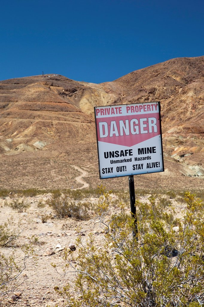 Stock Photo: 1566-1017053 Barstow, California - A sign warns visitors to stay away from unsafe mines in the Mojave Desert
