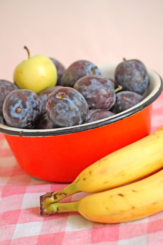 Stock Photo: 1566-1019844 Plums and a small green apple in a red metal bowl with bananas  Fresh purple plums in an enamel red bowl  Small green apple windfall  Bananas lay beside the bowl on red gingham cloth