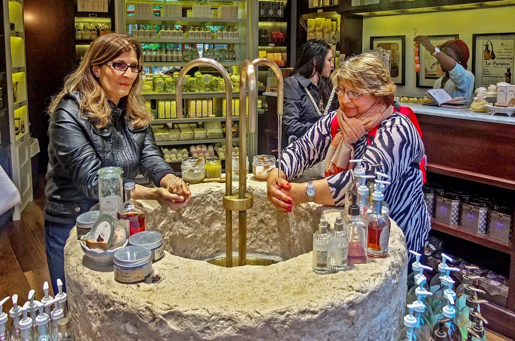 Stock Photo: 1566-1020187 At an imported French soap shop in midtown Manhattan, New York City, women customers try out the products at an ornate stone sink