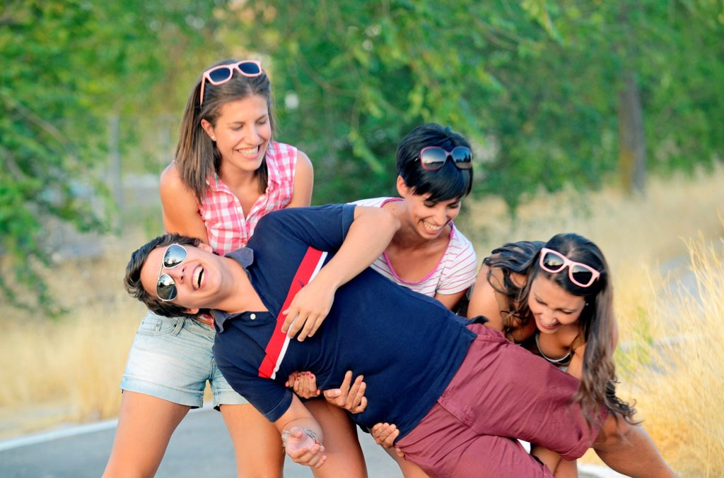 Stock Photo: 1566-1021037 Three young women trying to carry young man on their arms