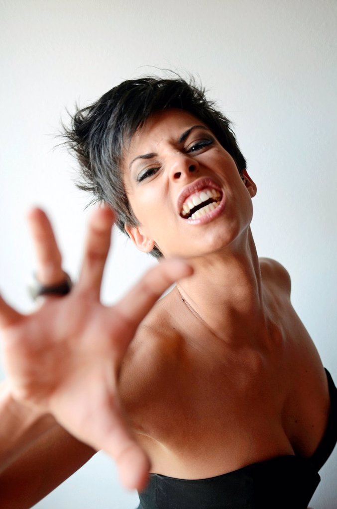 Stock Photo: 1566-1021068 Attractive short haired woman shows her nails in a feline attitude