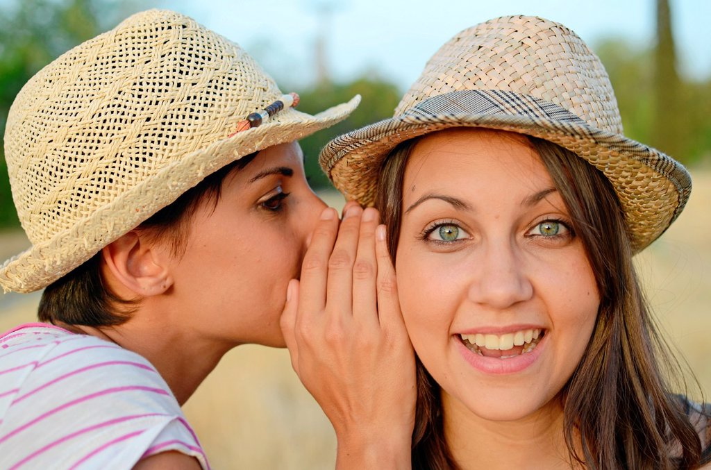 Stock Photo: 1566-1021937 Young woman whispers in friends ear