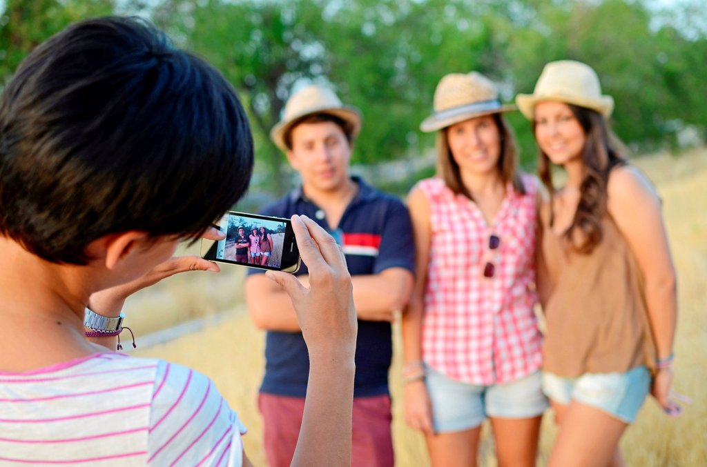 Young woman takes a photo of two girls and a boy, with mobile phone : Stock Photo