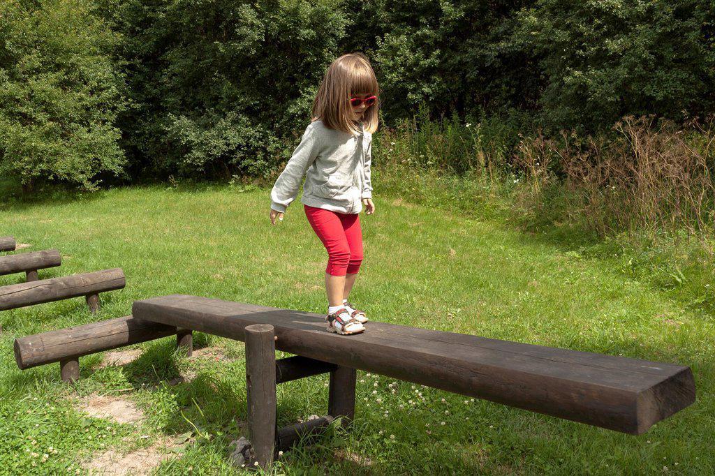 Girl walking on balance beam : Stock Photo