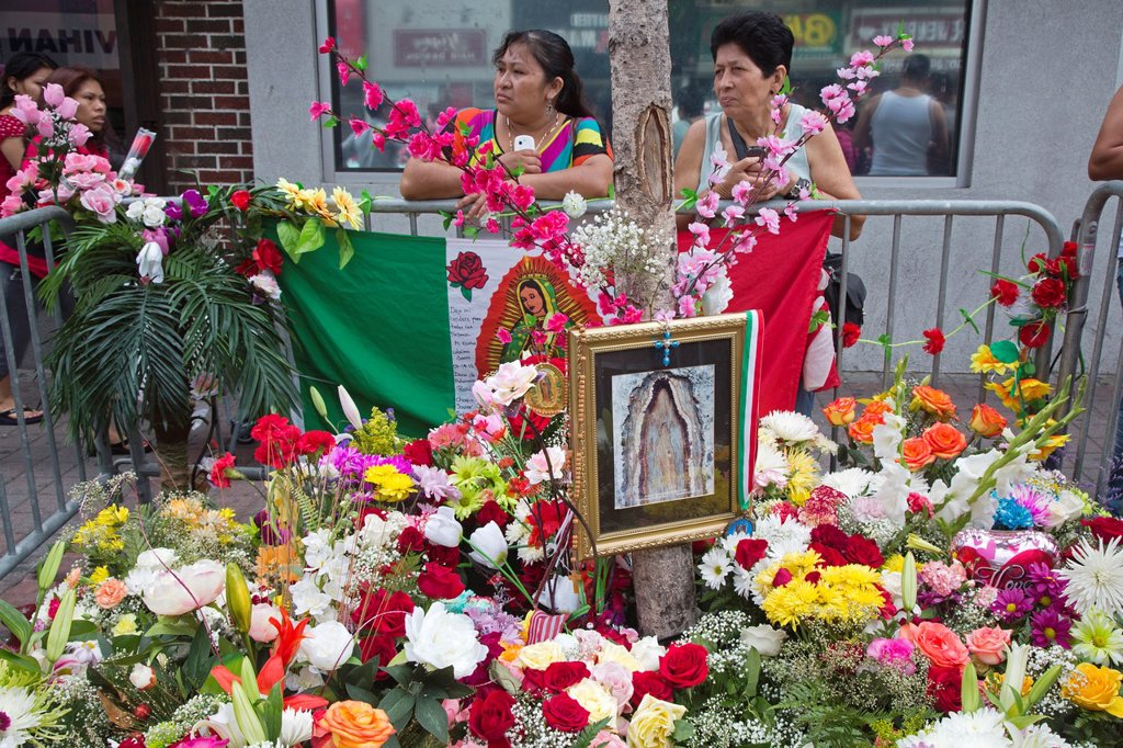 Stock Photo: 1566-1023416 West New York, New Jersey - A knot on a tree trunk, which many view as a miracle depicting the Virgin Mary, attracts crowds of mostly-Hispanic faithful who pray, light candles, and leave flowers