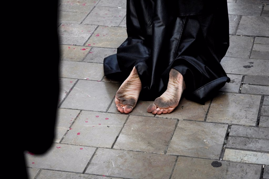 Stock Photo: 1566-1024814 The barefoot Holy Week participant kneels on the street during the Easter procession in Malaga, Spain, 7 April 2007