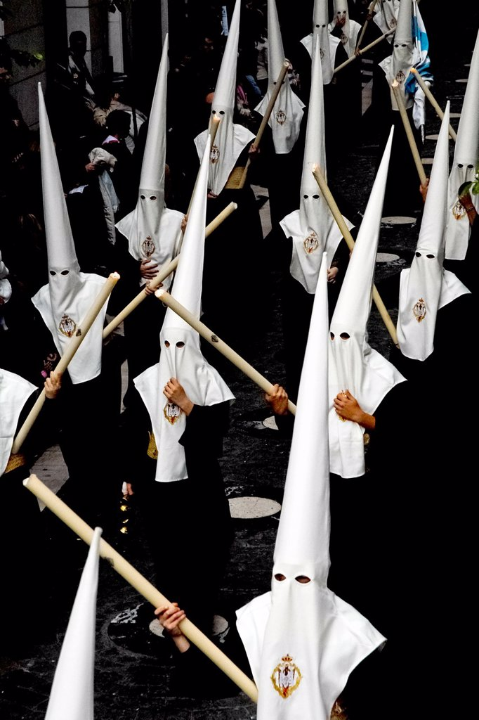 Stock Photo: 1566-1024816 The Holy Week penitents carry large processional candles in a narrow street during the Easter celebration in Malaga, Spain, 7 April 2007