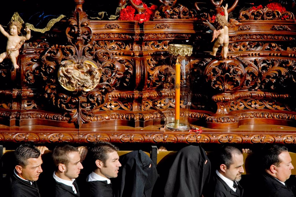 The wooden throne with fine carvings and sculptures is carried on the shoulders of the carriers during the Easter celebration in Malaga, Spain, 5 April 2007 : Stock Photo