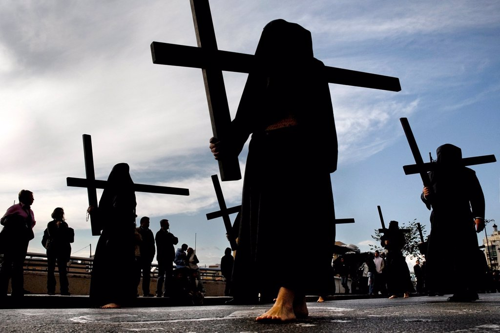 Stock Photo: 1566-1025299 The Holy Week participants Nazarenos demonstrate their penance by carrying rough wooden crosses in the processions during the Easter celebration in Malaga, Spain, 7 April 2007