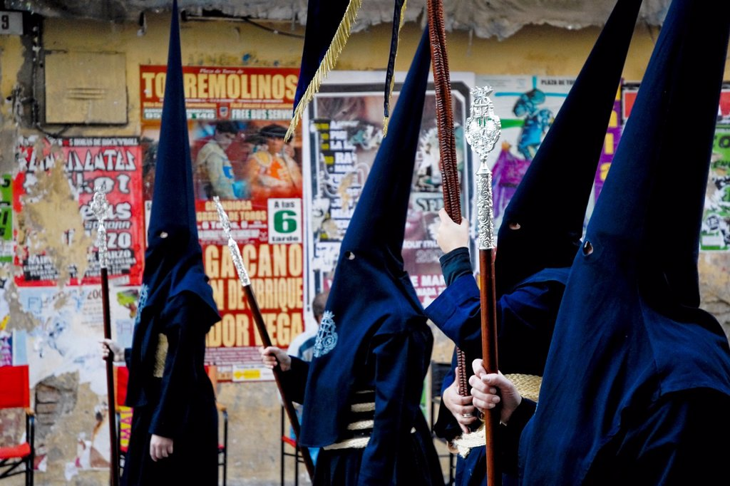Stock Photo: 1566-1025301 The Holy Week participants wearing a dark blue tunic and a hood with the conical hat walk down the street of Malaga, Spain, 5 April 2007