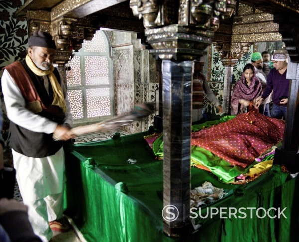 Stock Photo: 1566-1025599 Fatehpur Sikri, Uttar Pradesh, India  A Couple Visiting the Mausoleum of Sheikh Salim Chishti  Prayers are often offered in hopes of conceiving a child  Woman tosses rose petals on the tomb