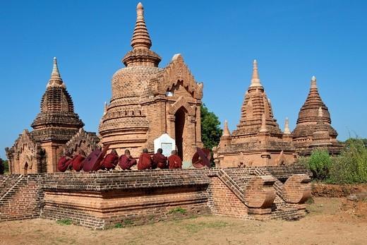 Myanmar, Burma  Bagan  Young Novice Monks Praying Outside a Temple : Stock Photo