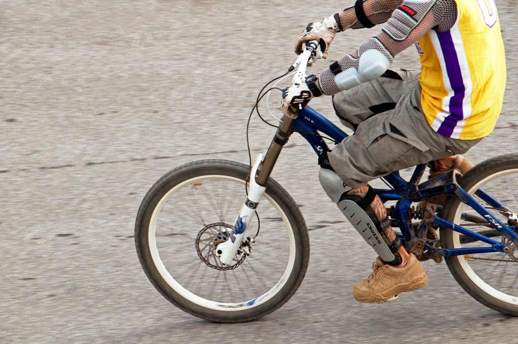 Stock Photo: 1566-1030414 well protected mountain biker with protectors on arms, elbows, forearms, knees, crossbones riding profesional mountain bike with disc brakes coming back from Alpine ride