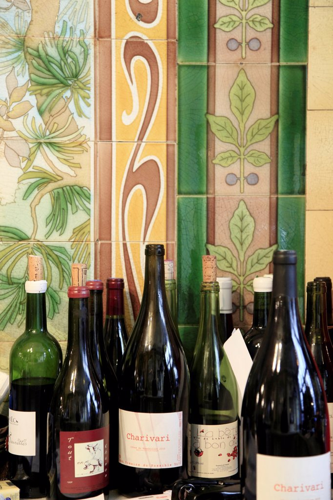 Art Nouveau style tiles decorations from a previous exotic bird shop in restaurant Vivan with bottles of organic wine in foreground  Paris  France : Stock Photo