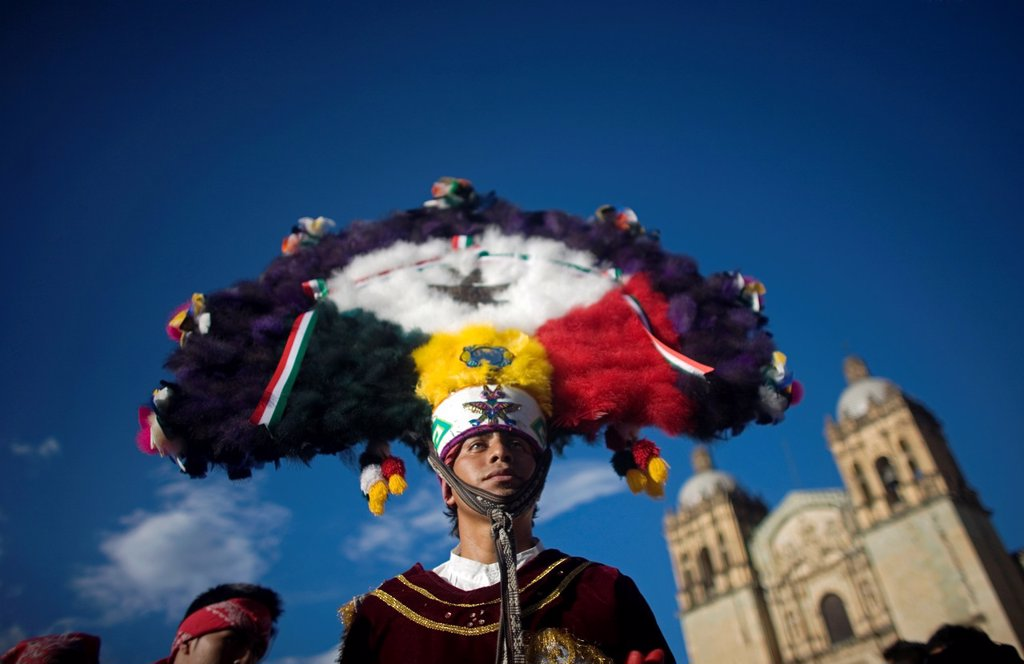 A dancer performs the Dance of the Feather or Danza de la Pluma during the Guelaguetza parade in front of the Santo Domingo church in Oaxaca, Mexico, July 21, 2012  Oaxaca commemorates the ´Guelaguetza,´ an annual celebration by all seven of the state´s r. A dancer performs the Dance of the Feather or Danza de la Pluma during the Guelaguetza parade in front of the Santo Domingo church in Oaxaca, Mexico, July 21, 2012  Oaxaca commemorates the ´Guelaguetza,´ an annual celebration by all seven of t : Stock Photo