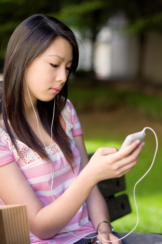 A young woman sitting on a park bench listening to her music player : Stock Photo
