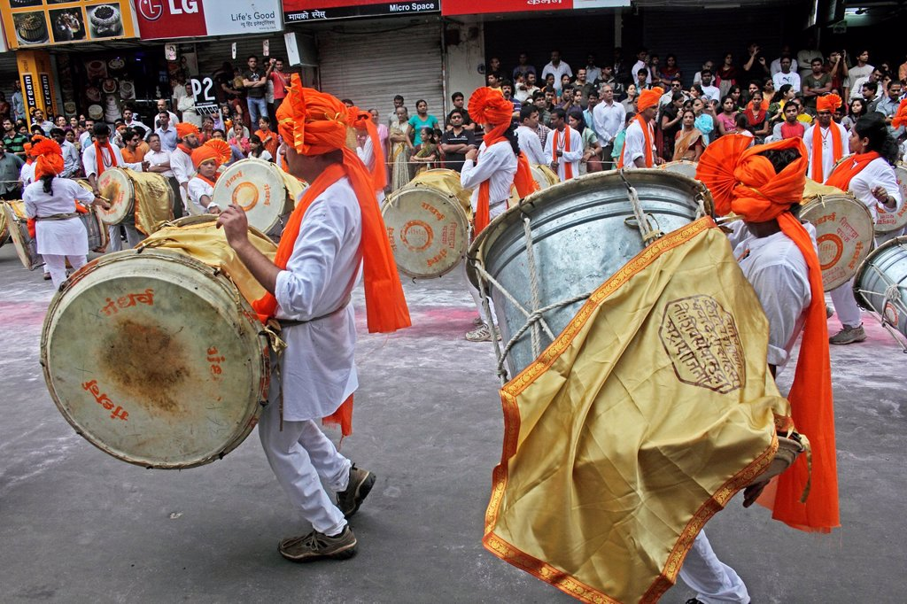 Indian girls & men wearing headgear called feta and white kurta pajamas and playing musical instrument called ´dhol-taash´ during Anant Chaturdashi Ganpati, Visarjan Miravnuk, Pune , Maharashtra , India : Stock Photo