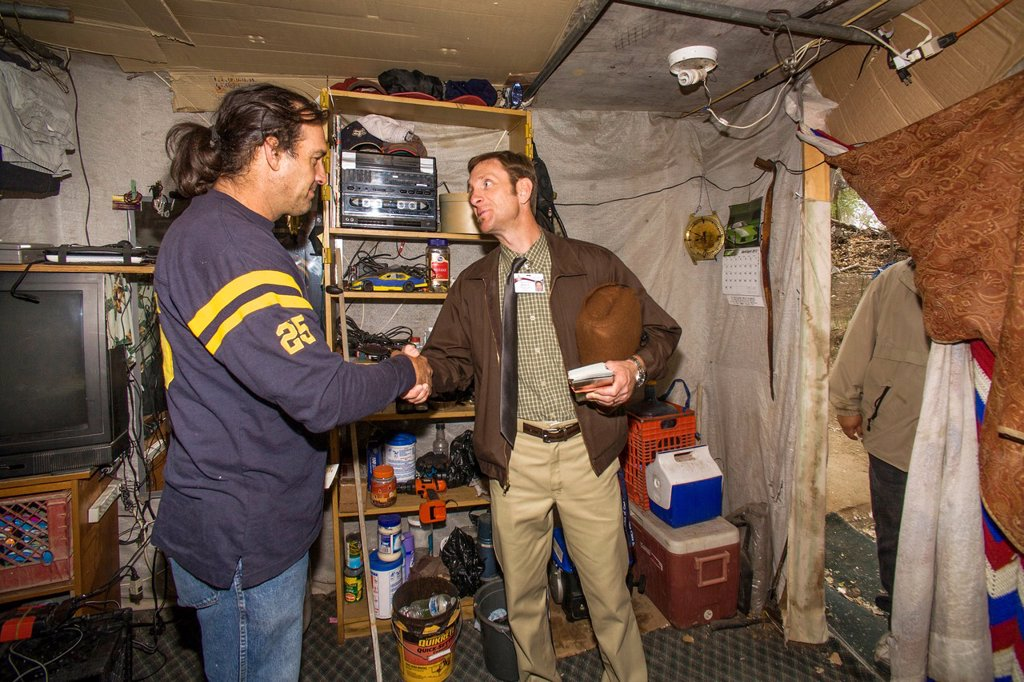 A local minister visits an indigent military veteran in a makeshift shelter among homeless residents of a primitive outdoor encampment in the desert town of Victorville, CA : Stock Photo