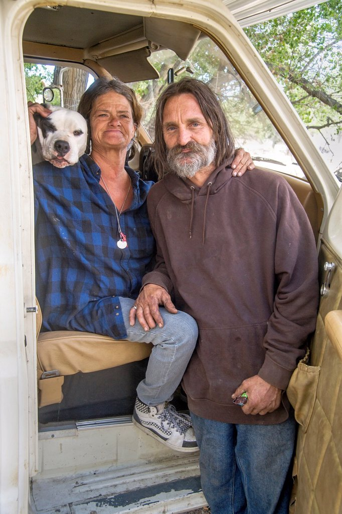An affectionate indigent couple and their dog live in a truck camper among homeless residents of a primitive outdoor encampment in the desert town of Victorville, CA : Stock Photo