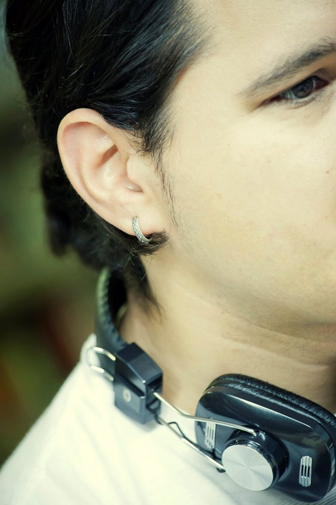 Young man with earphones and earring : Stock Photo